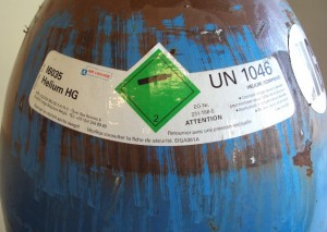 A tank of helium with warning label.