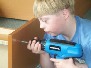 A boy using an electric drill