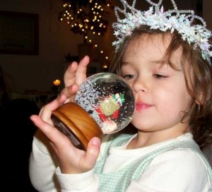 A young girl playing with a snow globe